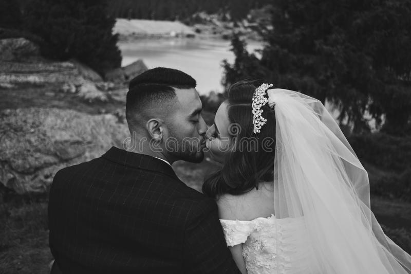 Black and white wedding photo of loving Kazakh Asian couple in nature, beautiful bride in dress and veil and groom in suit hug and royalty free stock photography