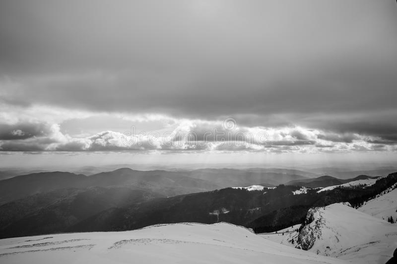 Black and white winter landscape over Carpathian Mountains. Panorama of snow mountain range landscape with light coming from sky stock image