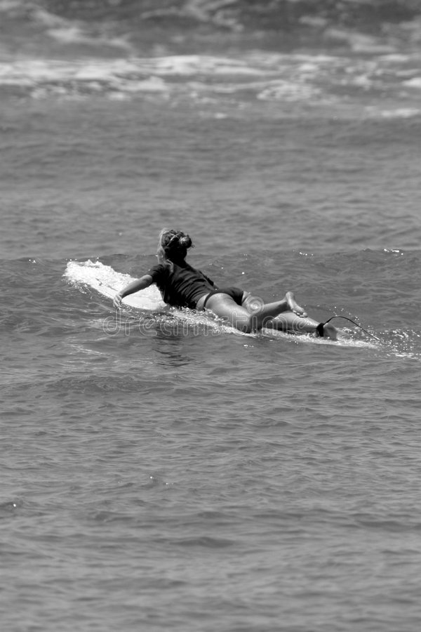 Black and White Woman Paddling a Surfboard royalty free stock photos