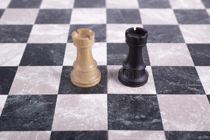 Black and white wooden rooks on chessboard. Black and white wooden rooks standing on chessboard stock photos