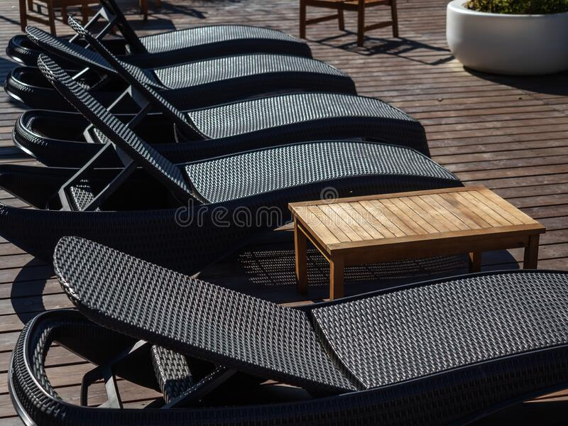 Black wicker sun loungers stand in a row on a wooden platform on the street. Black wicker sun loungers stand in a row on wooden platform on the street royalty free stock photo