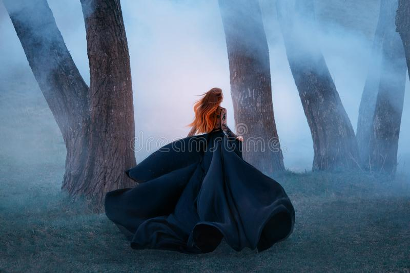 Black widow in a long dark silk lace dress, a girl with gorgeous light red hair runs off into a secret forest, the royalty free stock images