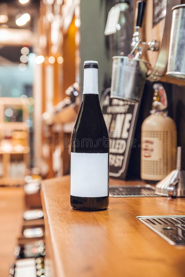 Black wine bottle with label and white cap in wine shop royalty free stock photos