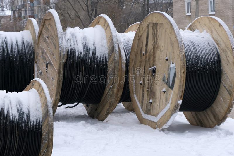 Black wire electric cable with wooden coil of electric cable under the sky. stock photo