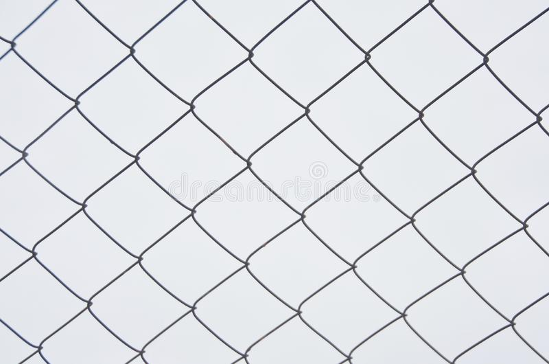 Decorative wire mesh. Black wire, rhombuses on a white background. Metal fencing. background of metal mesh, white royalty free stock images