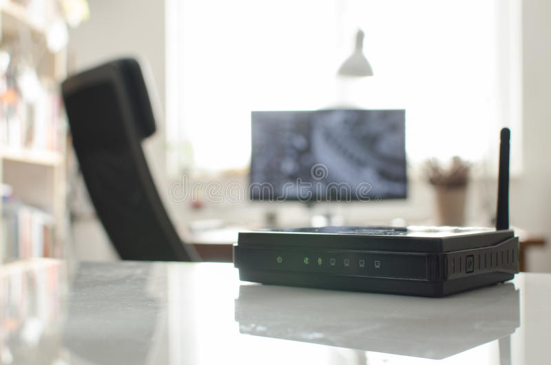 Black wireless router on white reflective table stock photography