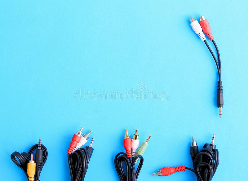 Black wires for computer and tv on blue background top view stock images