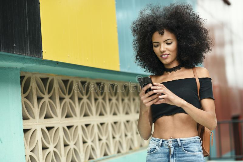 Black woman afro hair on the street holding a smartphone. Young black woman with afro hair walking on the street holding a smart phone. Female wearing casual royalty free stock photo
