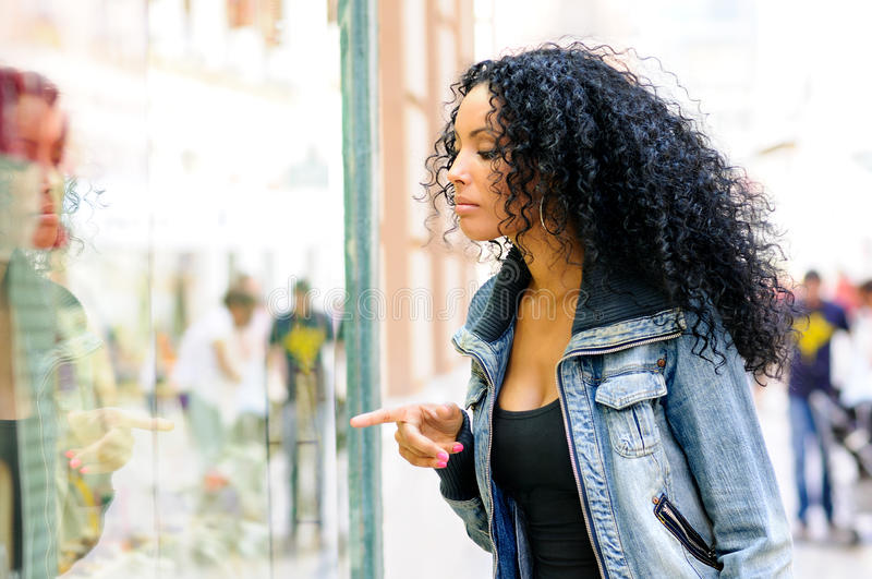 Black woman, afro hairstyle, looking at the shop window royalty free stock photography