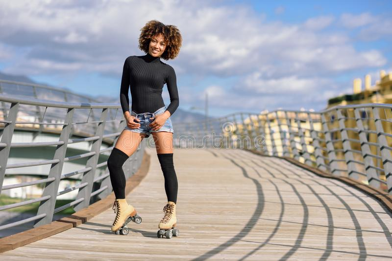 Black woman, afro hairstyle, on roller skates riding outdoors on urban bridge with open arms. Smiling young female rollerblading. On sunny day. Beautiful clouds stock images