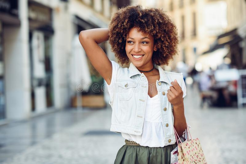 Black woman, afro hairstyle, with shopping bags in the street. stock photos