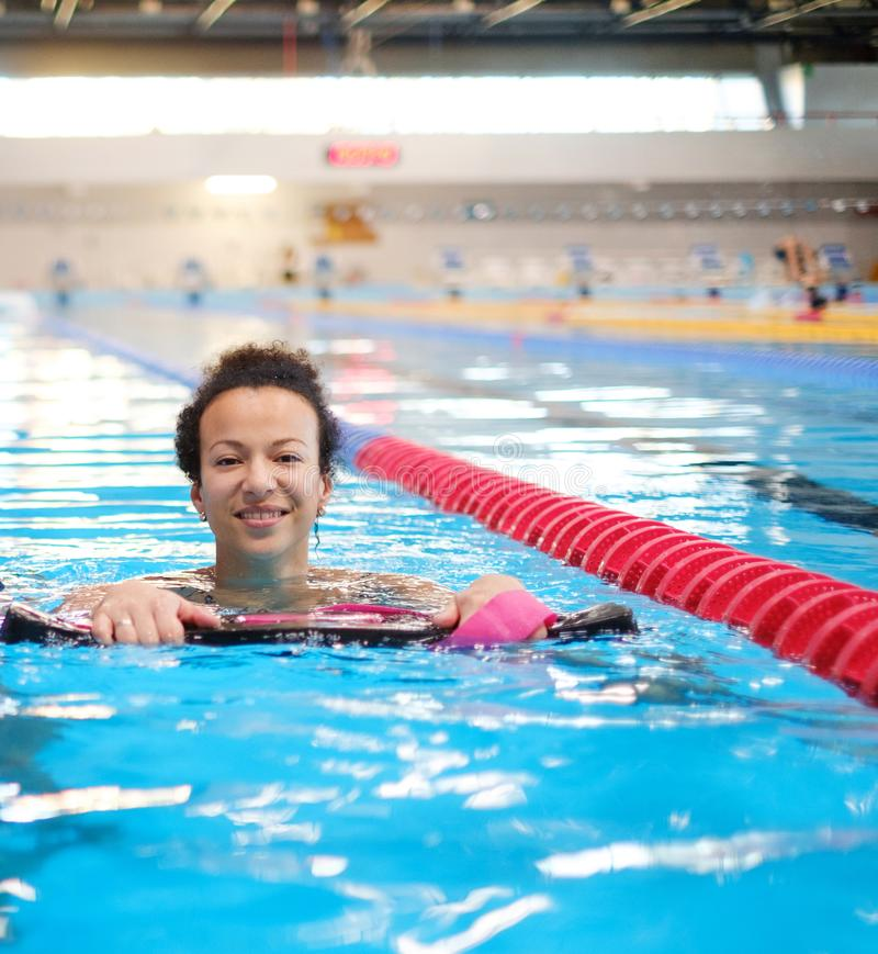 Black woman attending water aerobics class in a swimming pool stock photos