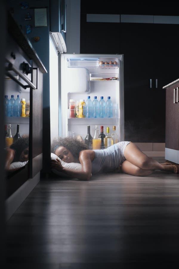 Black Woman Awake For Heat Wave Sleeping in Fridge stock photos