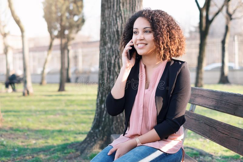 Black woman calling on mobile phone. In the city park royalty free stock image