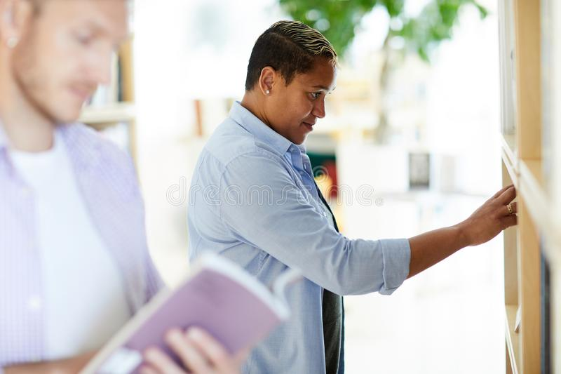 Black woman choosing book in bookstore. Curious portly young Black women in mens shirt standing in front of bookshelf and choosing book in bookstore royalty free stock image