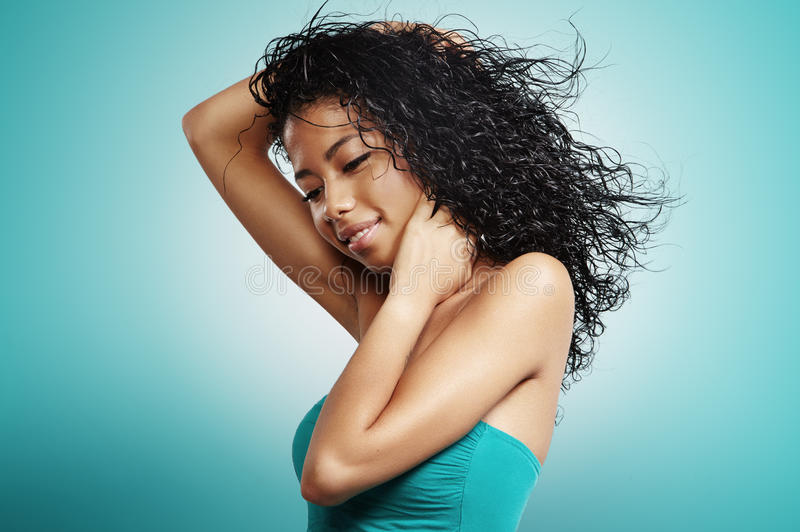 Black woman with curly hair and flying hair. On blue royalty free stock photo