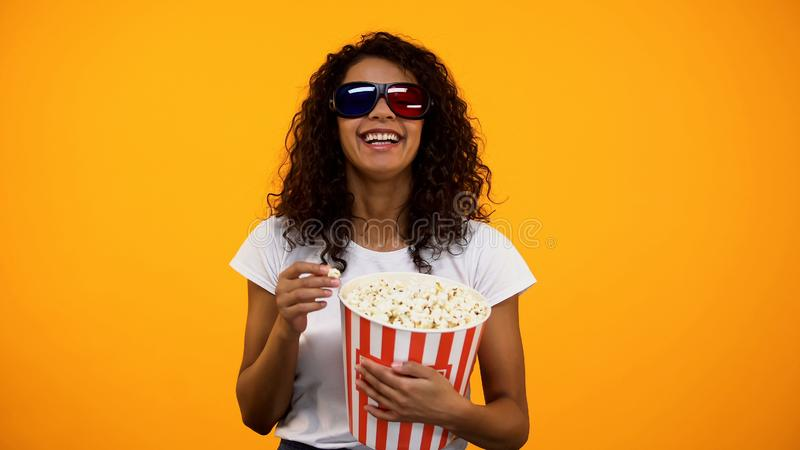 Black woman in 3d glasses eating popcorn and watching comedy movie, leisure royalty free stock image