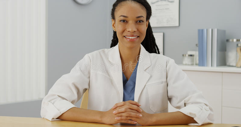 Black woman doctor sitting at desk smiling.  stock photography