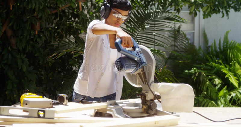 Black woman doing home improvement cutting wood with a table saw stock photography