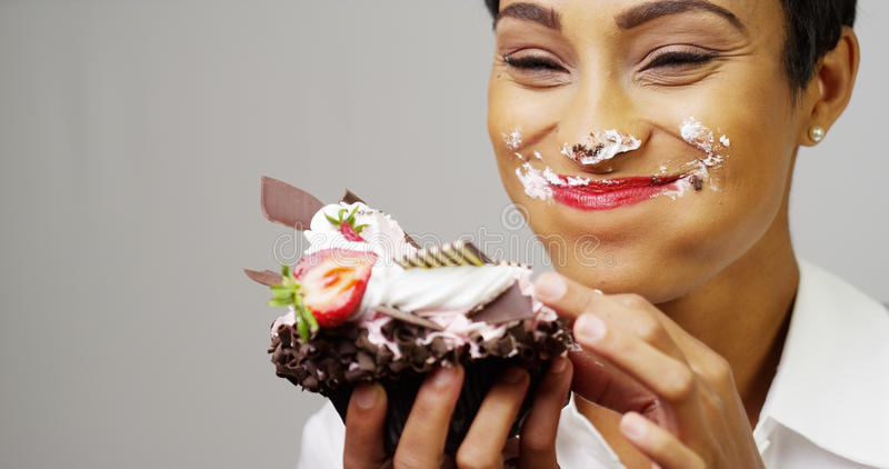 Black woman eating a huge fancy dessert royalty free stock photography