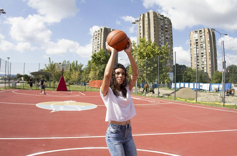 Black woman.Exercise free throw.On the basketball court. A young black woman from Africa with dark hair and black cap. White t-shirt and jeans.Exercise free stock image