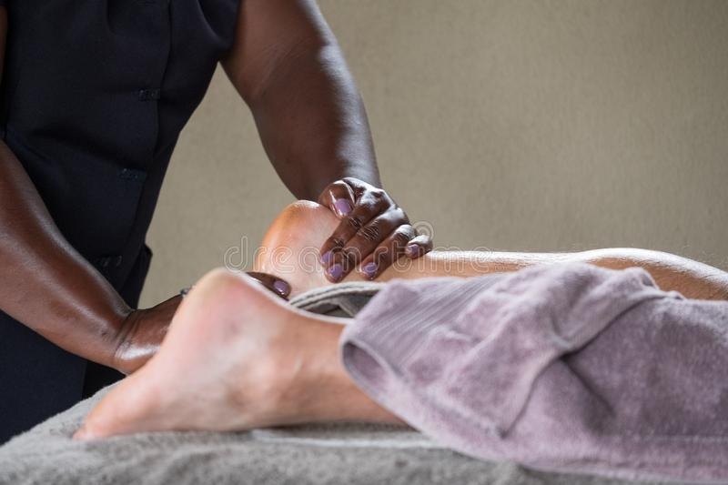 Black woman gives a foot massage to an elderly Caucasian man. Black woman gives a relaxing foot massage to an elderly Caucasian man royalty free stock photo