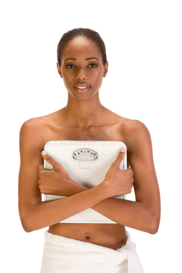 Black woman holding weight scales in front of her stock photos