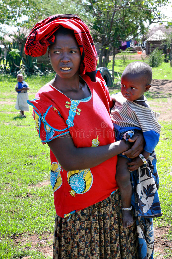 Free Black Woman In Shabby Clothes, Holds A Child. Stock Photo - 50269440