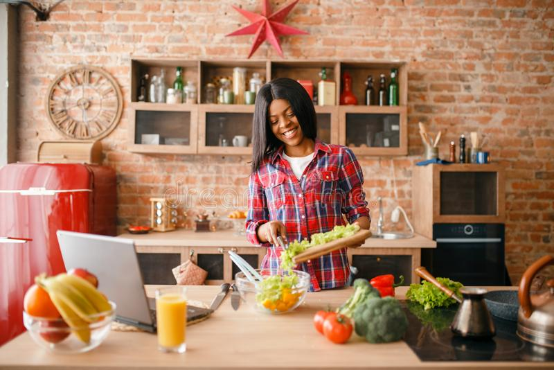 Black woman looking recipe on laptop royalty free stock photos