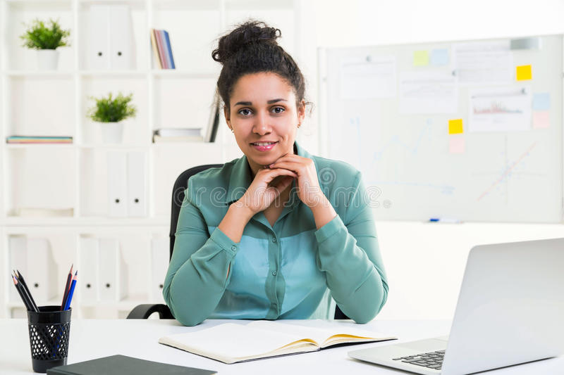 Black woman in office. Attractive african american woman sitting at office desk with laptop, stationery items, looking at the camera and smiling royalty free stock photo