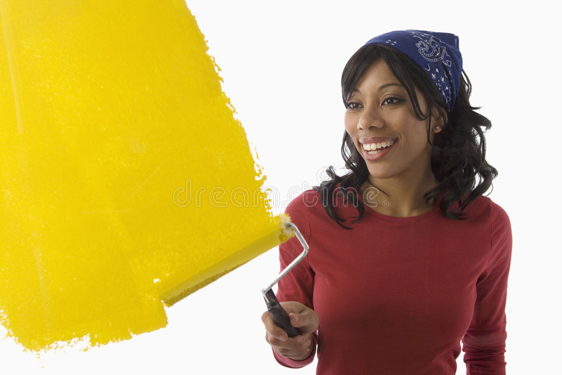 Black woman painting walls. Beautiful Young African American woman painting the wall yellow royalty free stock photo