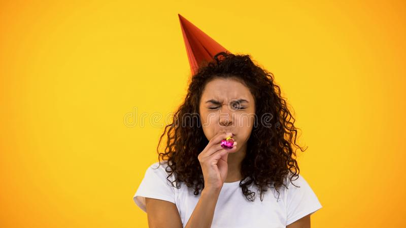 Black woman in party hat blowing noisemaker, celebrating birthday, holiday party royalty free stock images