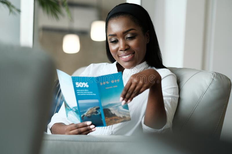Black Woman Reading Travel Flyer For Holiday Trip stock photography