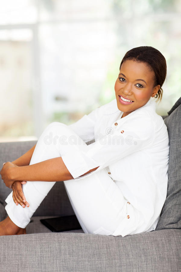 Black woman relaxing. Beautiful young black woman relaxing on a couch at home stock photo