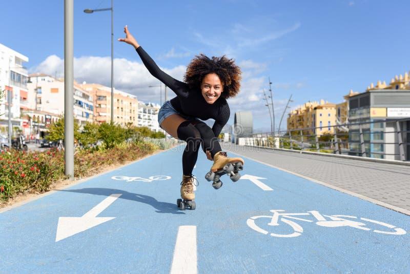 Black woman on roller skates riding on bike line stock photos