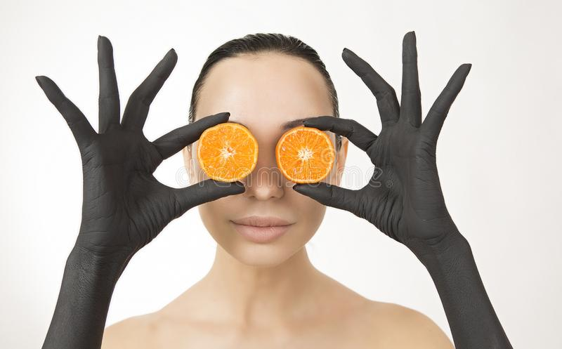 Black woman`s hands holding orange halves near her face. Black hands with bright tasty mandarin. Creative colorful art concept. Portrait of a young woman royalty free stock photography