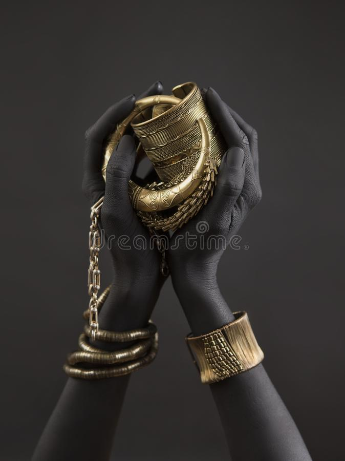 Free Black Woman`s Hands With Gold Jewelry. Oriental Bracelets On A Black Painted Hand. Gold Jewelry Royalty Free Stock Photography - 135827087