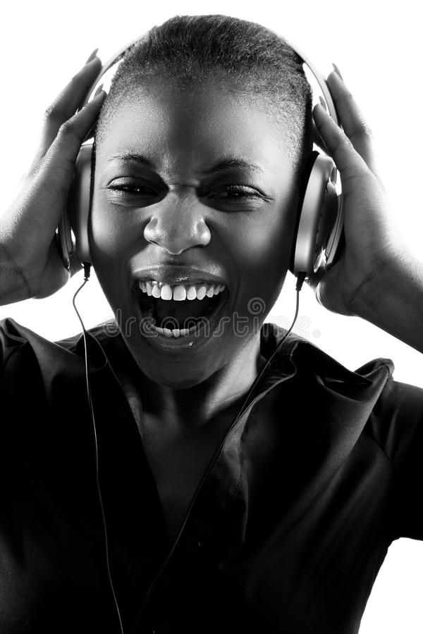 Black woman singing to music on headphones stock photography