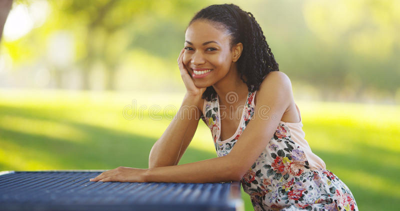 Black woman sitting on a park bench smiling royalty free stock photography