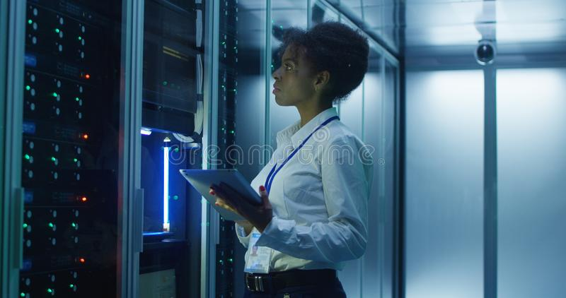 Black woman with tablet working in server room royalty free stock images
