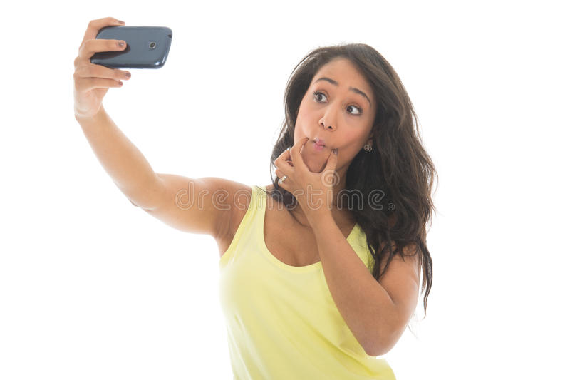 Black woman taking mad selfie. Young attractive black woman is taking a mad selfie with her cellphone isolated over white background stock photos