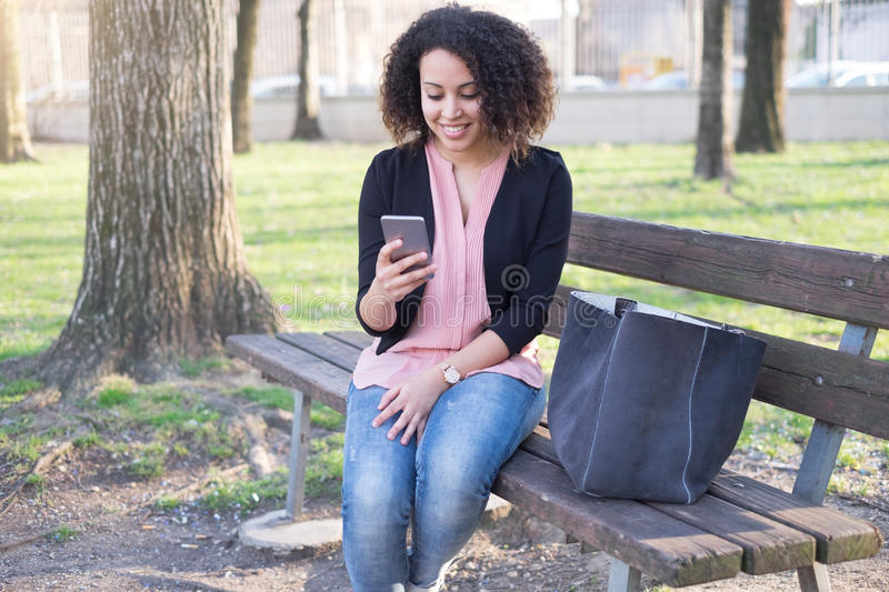 Black woman using app on mobile phone stock photography