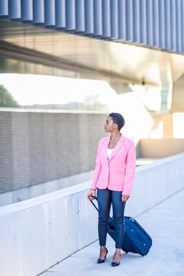 Black woman walking with travel bag wearing pink jacket. stock photos