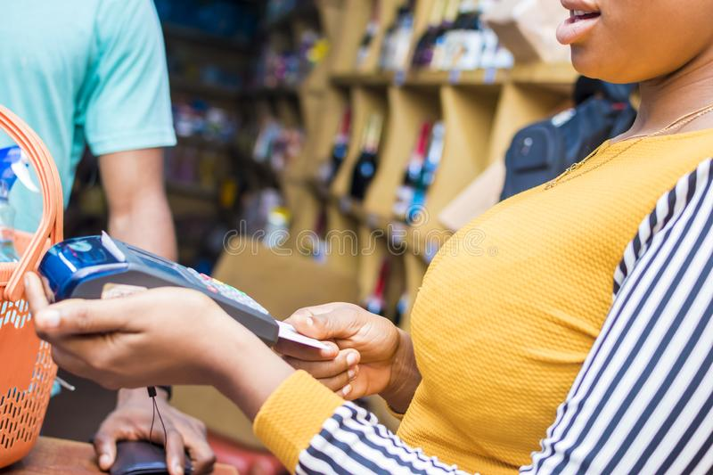 black woman working in a retail store using a point of sale machine to process payment royalty free stock photography