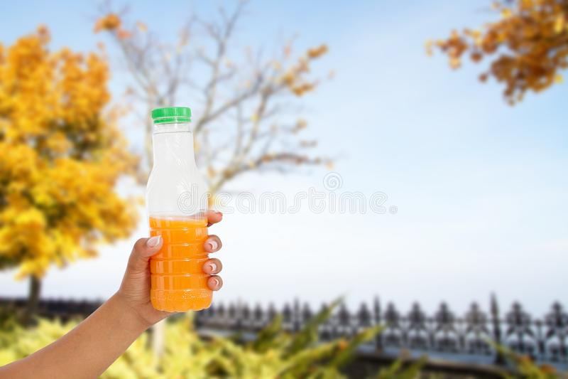 Black womans hand hold juice bottle on blurred park background, healthy lifestyle concept.  stock photography