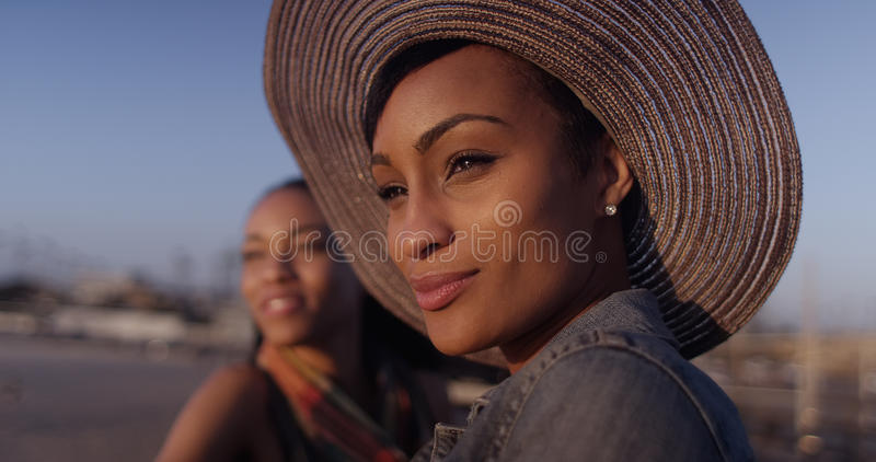 Black women best friends looking out over ocean while standing o royalty free stock image