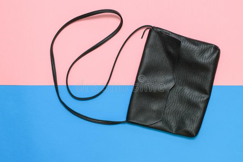 Black women`s bag with strap on pink and blue background. Modern women`s leather accessory. Flat lay royalty free stock images
