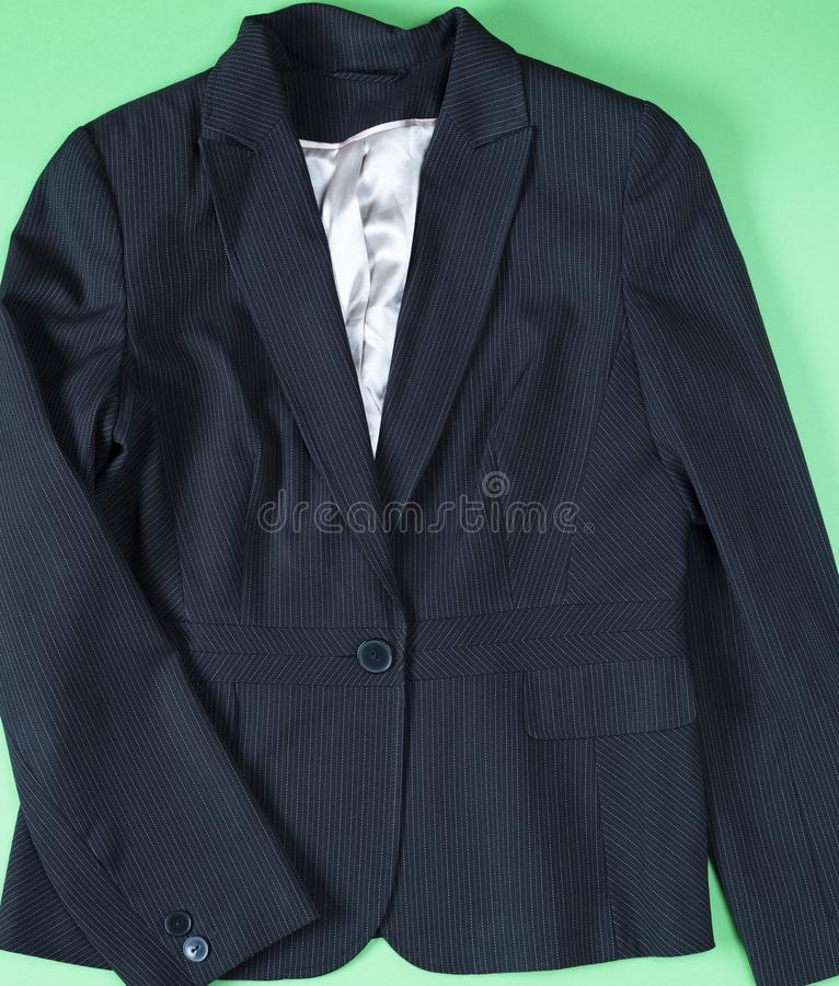 Black women`s jacket with long sleeves. On a green background stock images
