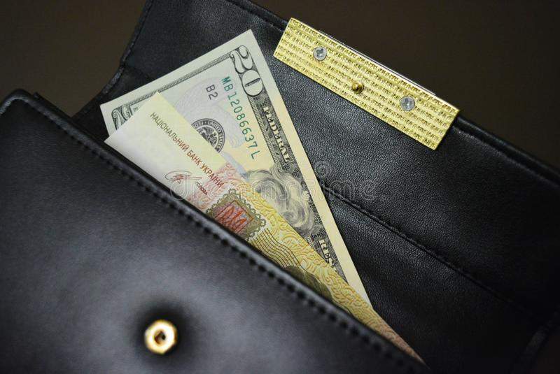 A black women`s purse with money made from genuine cowhide leather and gold accessories is located on a matte brown background. stock photos