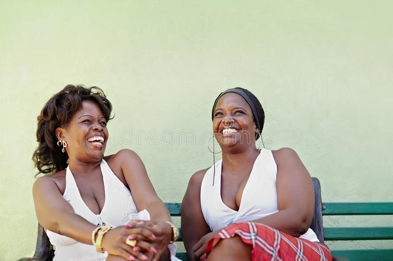 Black women with white dress laughing on bench royalty free stock images